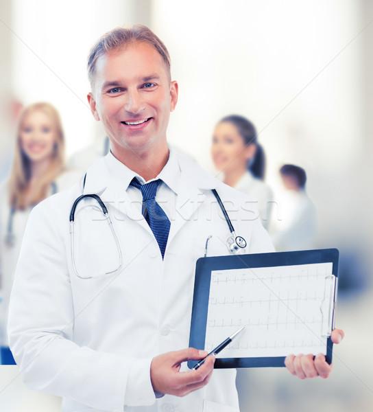 male doctor with stethoscope showing cardiogram Stock photo © dolgachov