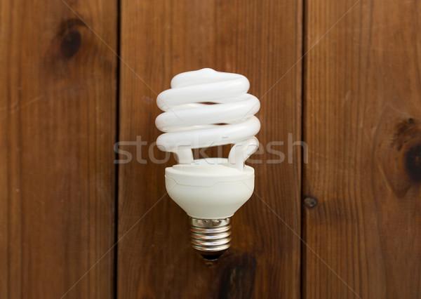 close up of energy saving lighting bulb on wood Stock photo © dolgachov