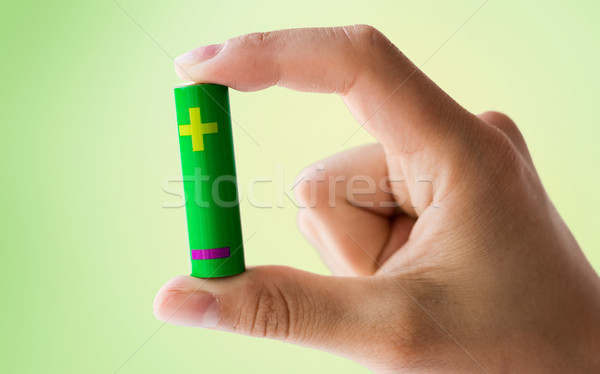close up of hand holding green alkaline battery Stock photo © dolgachov