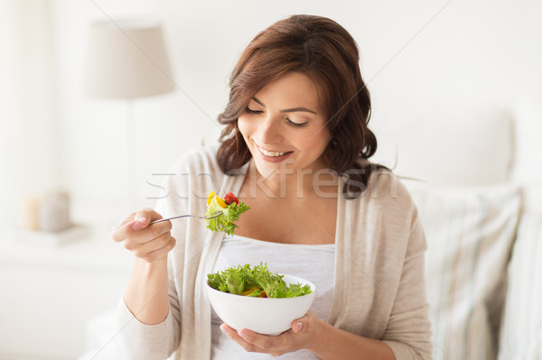 Stock photo: smiling young woman eating salad at home