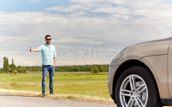 man hitchhiking and stopping car at countryside Stock photo © dolgachov