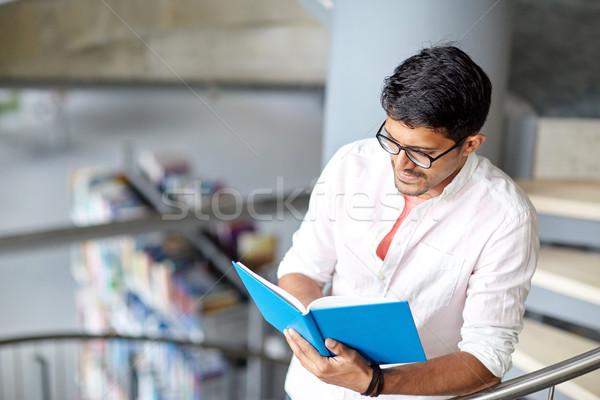 hindu student boy or man reading book at library Stock photo © dolgachov