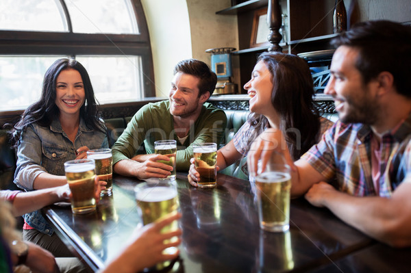 happy friends drinking beer at bar or pub Stock photo © dolgachov