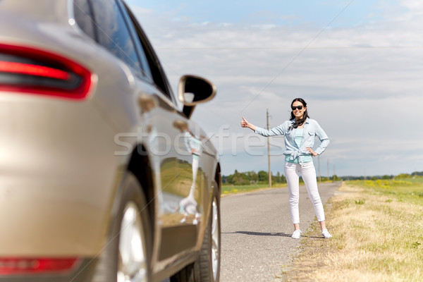Stock photo: woman hitchhiking and stopping car at countryside