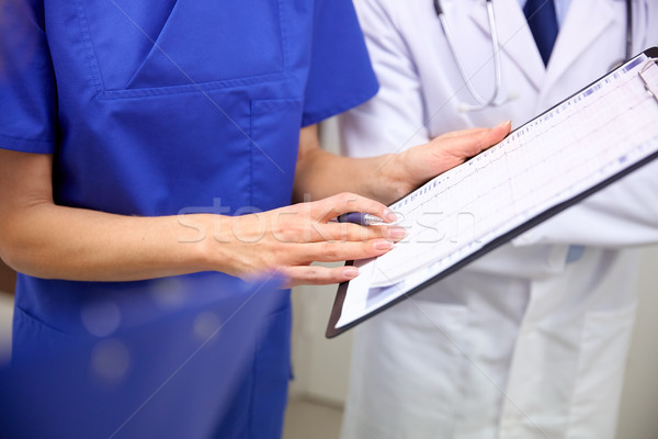 Stock photo: close up of doctors with clipboard at hospital