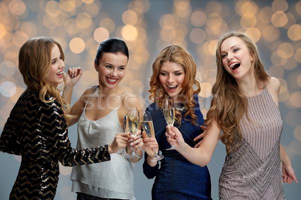 happy women clinking champagne glasses over lights Stock photo © dolgachov