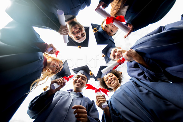 happy students or bachelors with diplomas Stock photo © dolgachov