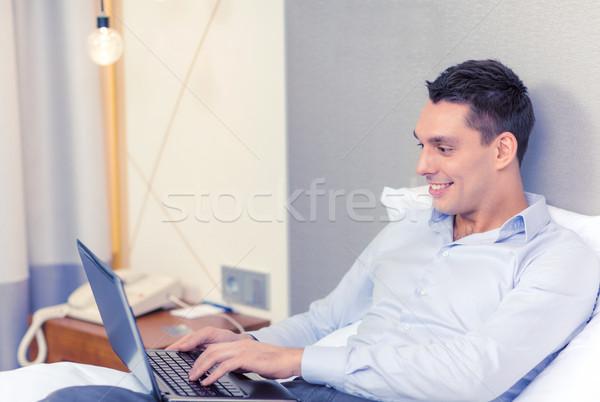 Heureux femme d'affaires portable chambre d'hôtel affaires technologie Photo stock © dolgachov