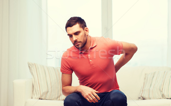 unhappy man suffering from backache at home Stock photo © dolgachov