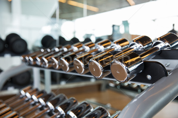 dumbbells and sports equipment in gym Stock photo © dolgachov