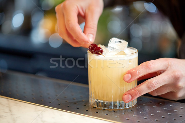 bartender with glass of cocktail and cherry at bar Stock photo © dolgachov