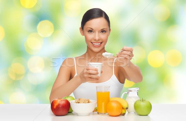 Szczęśliwy kobieta owoce zboża jedzenie jogurt Zdjęcia stock © dolgachov