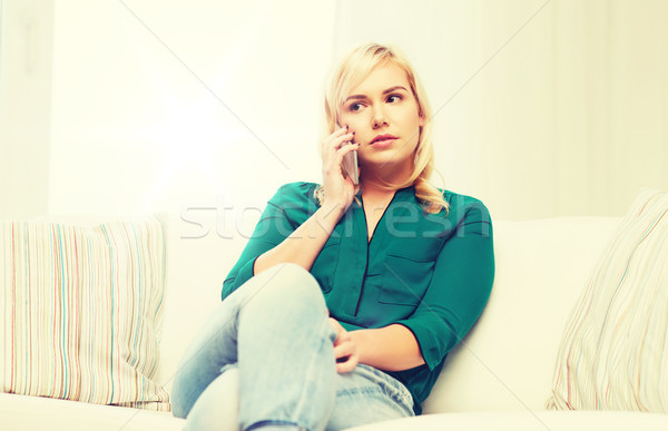 young woman calling on smartphone at home Stock photo © dolgachov