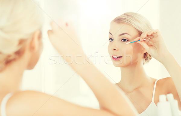 woman fixing makeup with cotton swab at bathroom Stock photo © dolgachov