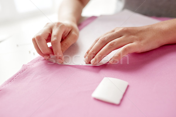 woman with pins stitching paper pattern to fabric Stock photo © dolgachov
