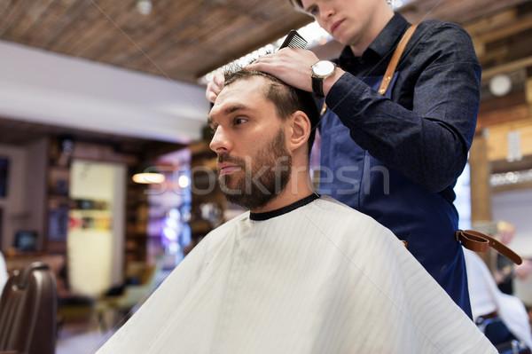 man and barber cutting hair at barbershop Stock photo © dolgachov