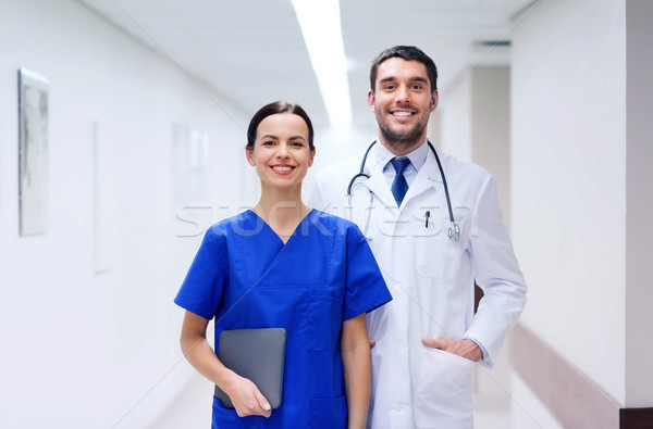 smiling doctor in white coat and nurse at hospital Stock photo © dolgachov