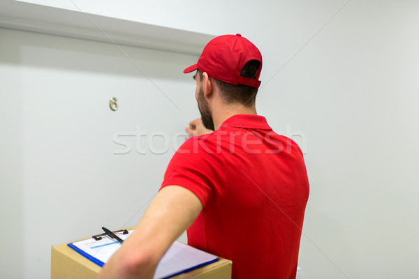 delivery man with parcel box knocking door Stock photo © dolgachov