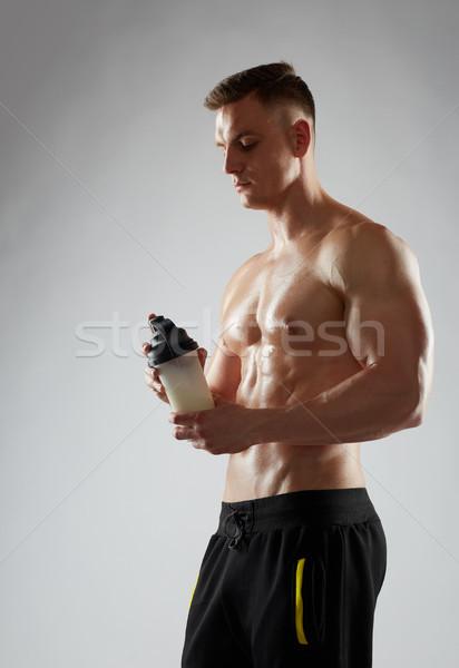 молодым человеком Культурист белок Shake бутылку спорт Сток-фото © dolgachov