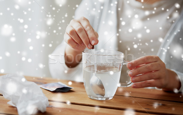 ill woman stirring medication in cup with spoon Stock photo © dolgachov
