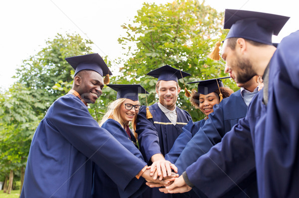Stock photo: happy students or bachelors in mortar boards