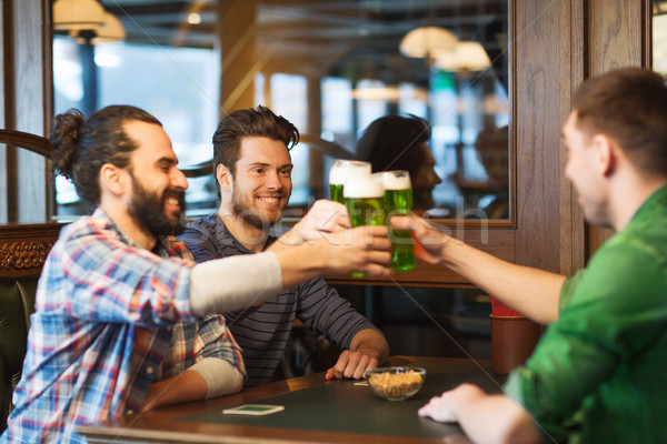 male friends drinking green beer at bar or pub Stock photo © dolgachov