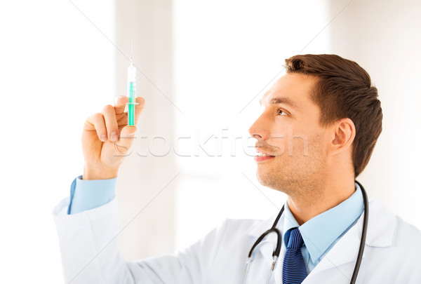 male doctor holding syringe with injection Stock photo © dolgachov
