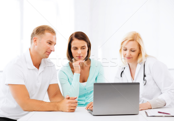 doctor with patients looking at laptop Stock photo © dolgachov