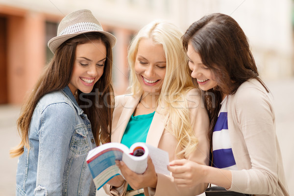 beautiful girls looking into tourist book in city Stock photo © dolgachov