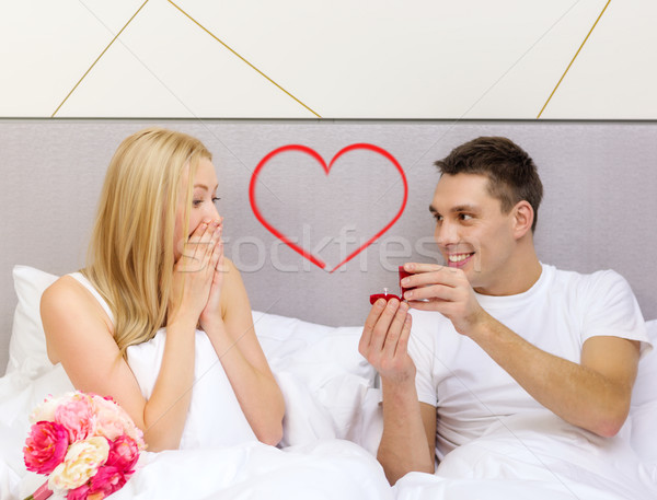 man giving woman little red box and ring in it Stock photo © dolgachov
