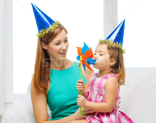 mother and daughter in blue hats with pinwheel Stock photo © dolgachov