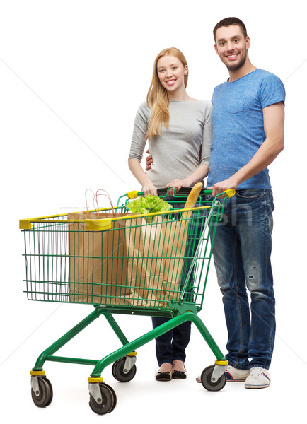smiling couple with shopping cart and food in it Stock photo © dolgachov