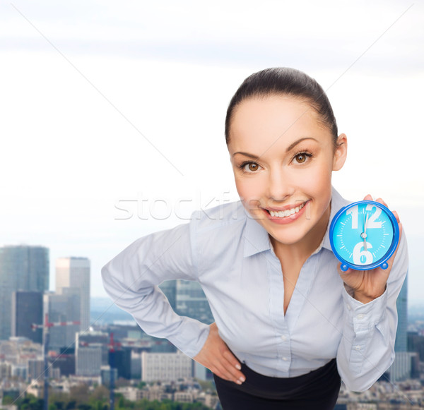 smiling businesswoman with blue clock Stock photo © dolgachov