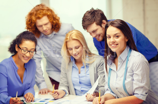 smiling creative team looking over clothes designs Stock photo © dolgachov