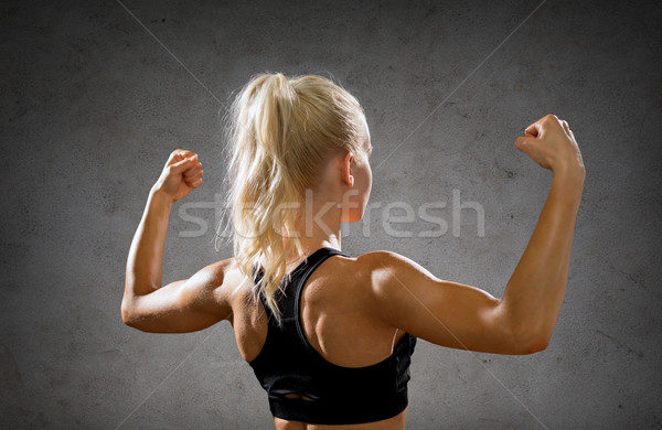 sporty woman from the back flexing her biceps Stock photo © dolgachov