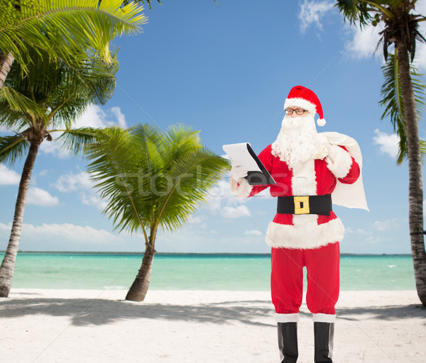 man in costume of santa claus with notepad and bag Stock photo © dolgachov