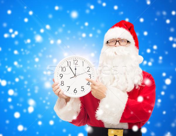 man in costume of santa claus with clock Stock photo © dolgachov