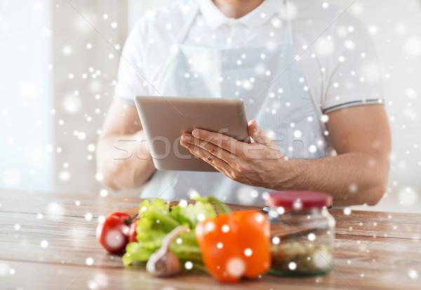 closeup of man reading recipe from tablet pc Stock photo © dolgachov