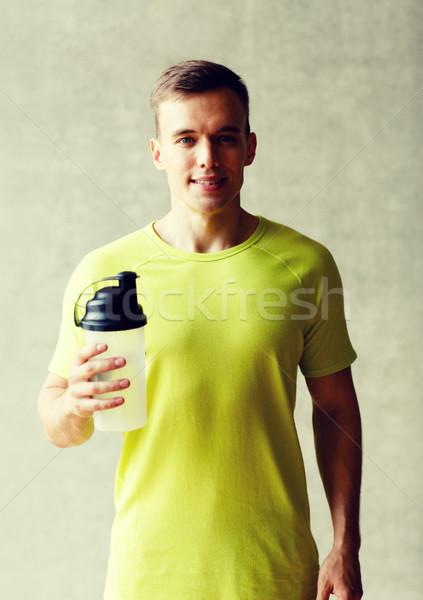 smiling man with protein shake bottle Stock photo © dolgachov