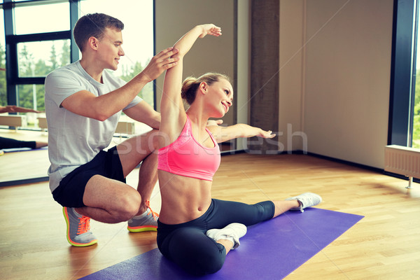 smiling woman with male trainer exercising in gym Stock photo © dolgachov
