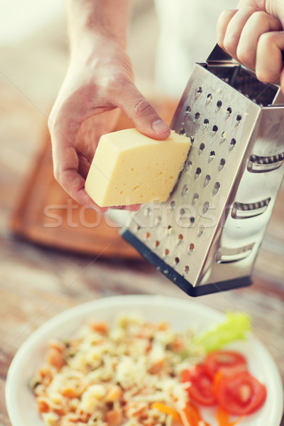 Stock photo: close up of male hands grating cheese over pasta