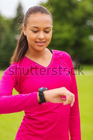 smiling young woman with heart rate watch Stock photo © dolgachov
