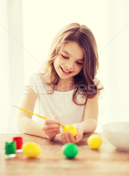 smiling little girl coloring eggs for easter Stock photo © dolgachov