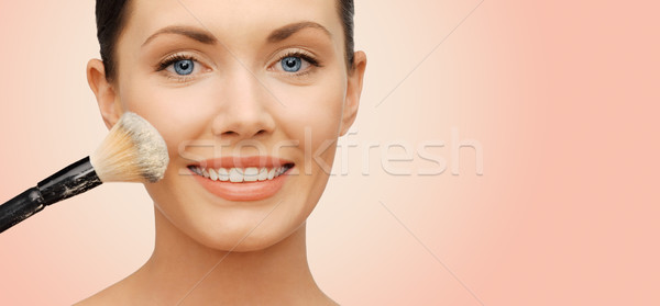 happy woman applying powder foundation with brush Stock photo © dolgachov