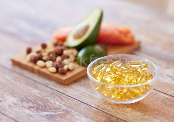 close up of omega 3 capsules and food on table Stock photo © dolgachov