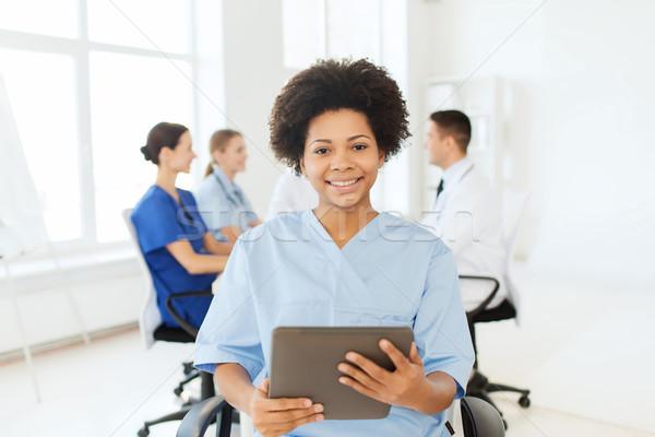 happy nurse with tablet pc over team at hospital Stock photo © dolgachov