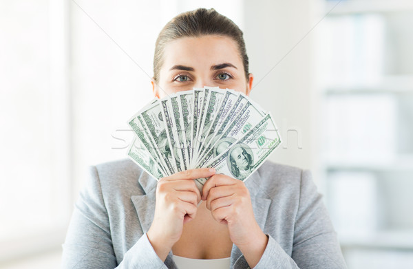 Stock photo: woman hiding her face behind us dollar money fan