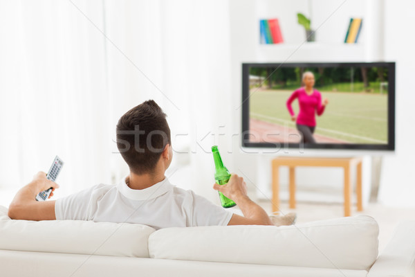 man watching sport on tv and drinking beer at home Stock photo © dolgachov