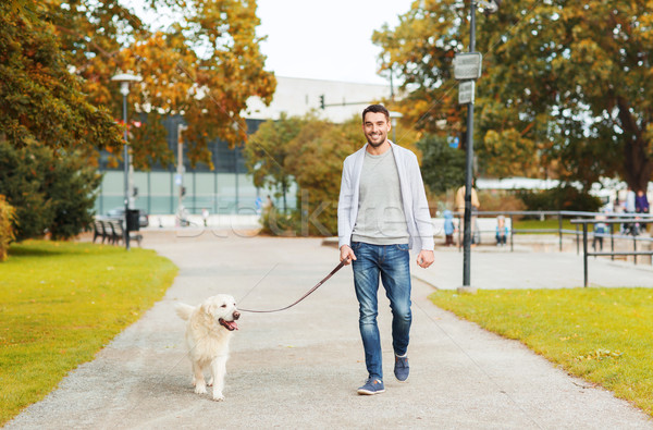 Stock photo: happy man with labrador dog walking in city park