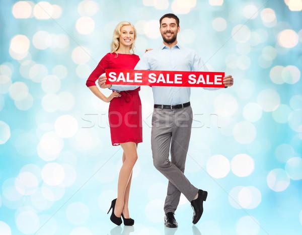 Szczęśliwy para czerwony sprzedaży podpisania niebieski Zdjęcia stock © dolgachov
